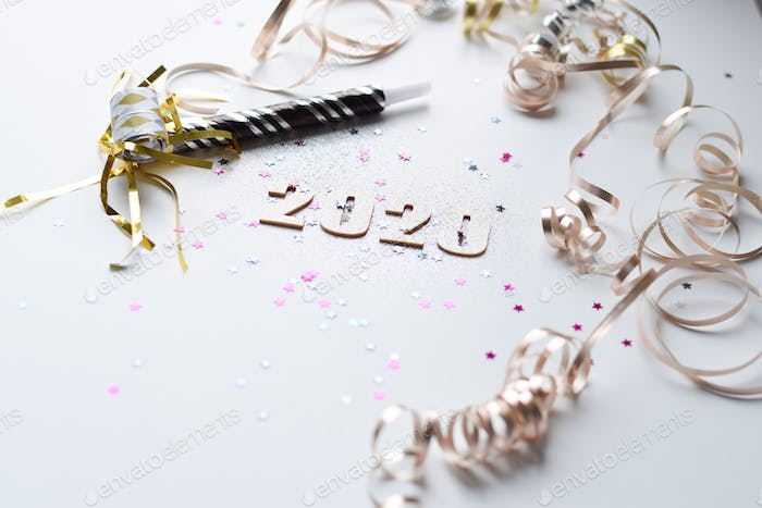 Happy New Year 2020 with glitter, star sprinkles and party favors on white background