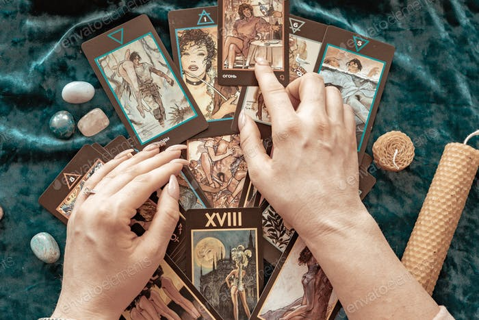 tarot cards in the hands of a young woman, candles and runes on a blue velvet background