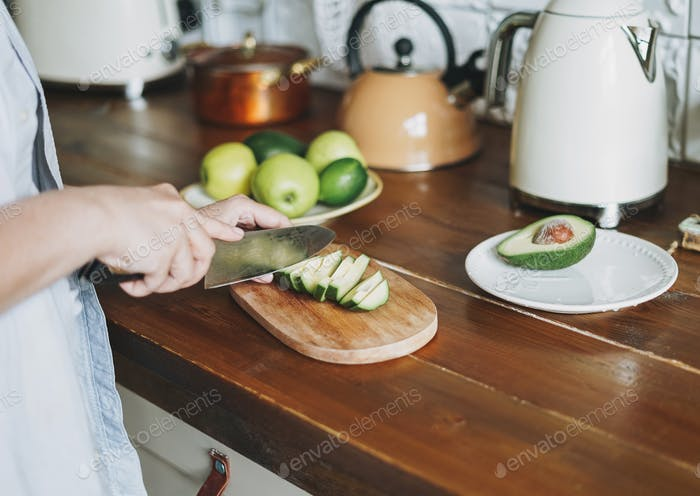 Female hands cut avocado on wooden working surface in kitchen at home