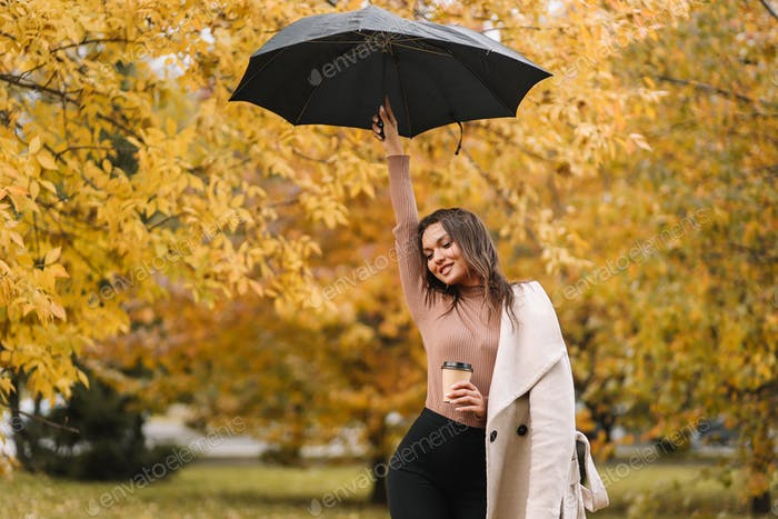 A happy girl holding a black umbrella walks in the rain in an autumn park in nature