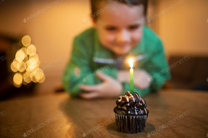 happy birthday boy looking at a lighted candle