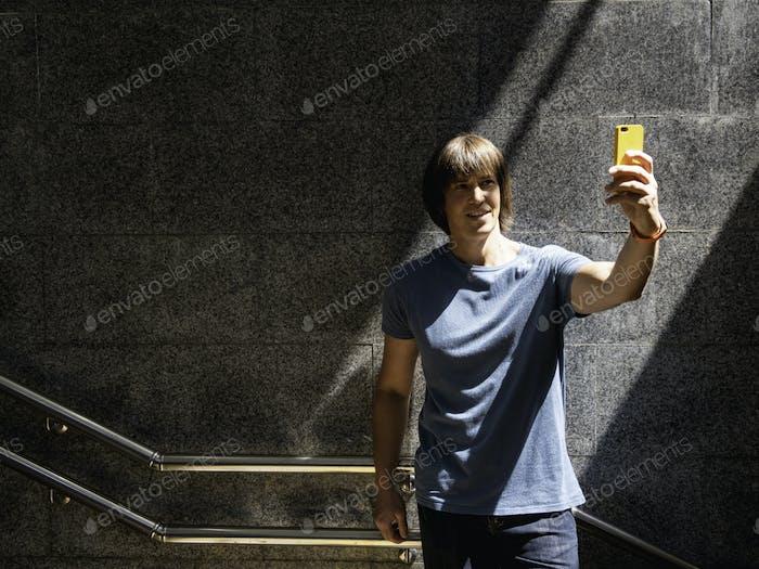Man makes selfie on his smartphone in underground pedestrian crossing.