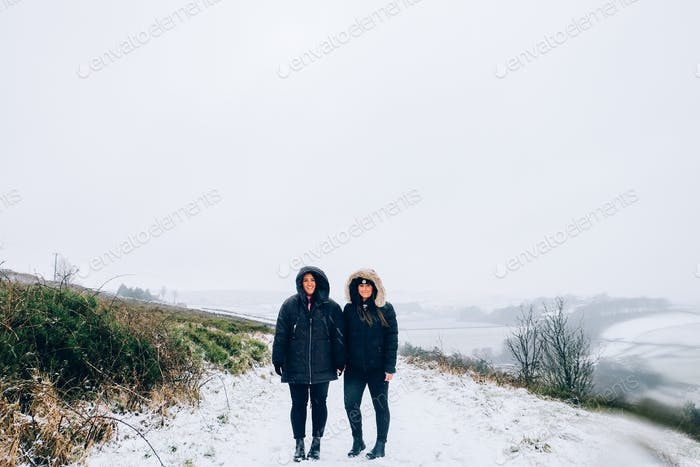 Girls holding hands in the snow in Yorkshire, United Kingdom