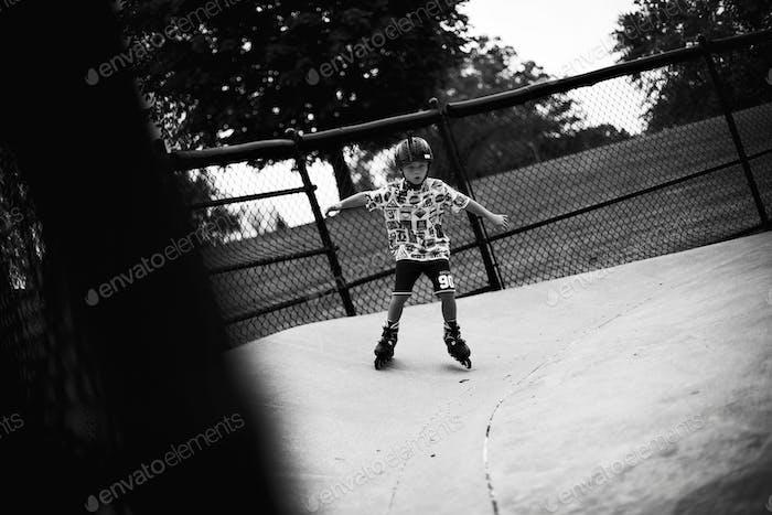 Little boy skating his heart out at skate park. Skating with Roller-skates.