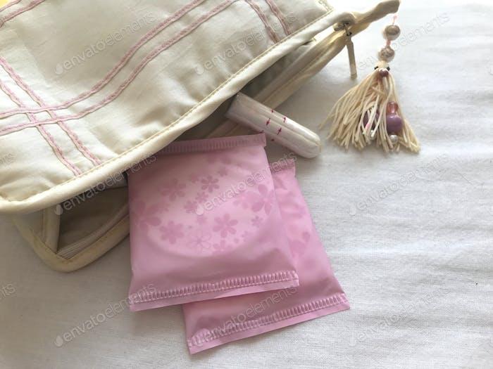 Frauengesundheit: Menstruation. Hygienepads und ein Tampon in einem Waschbeutel