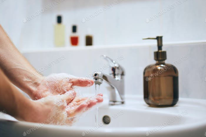 Washing hands at home in bathroom. Healthy lifestyle, hygiene and prevention viral and bacterial dis