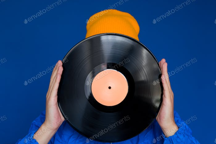 young man in a blue sport 90s style jacket and yellow hat holding vinyl record
