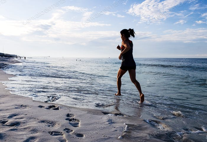 A very fit woman runner is running for exercise on the beach in the water of the ocean headed toward