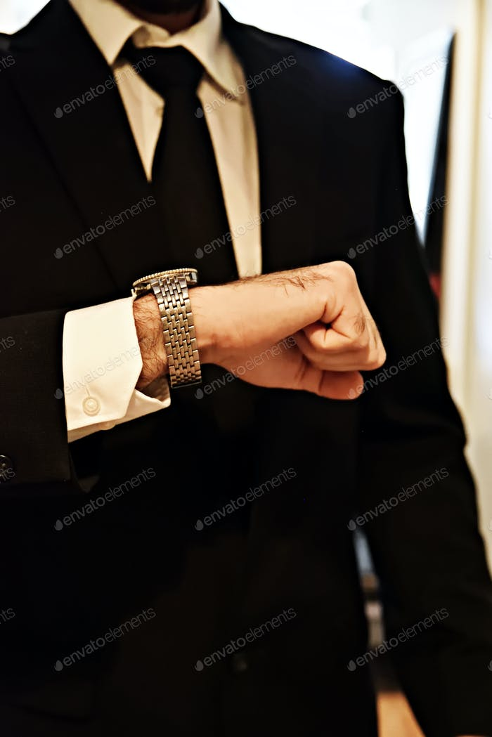 Torso of professional male checking his wristwatch. RLTheis