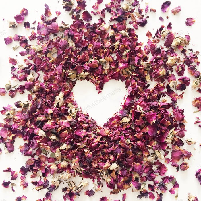 Dried rose petals with heart in negative space.