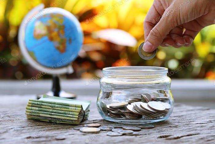 Menschen setzen Münzen in Glas und Geldbank mit Burry Weltkugelkarte Nahaufnahme Hintergrund