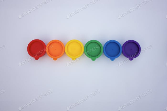 Rainbow row of bright and colorful paints against white background