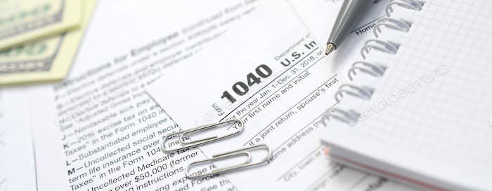 The pen, notebook and dollar bills is lies on the tax form 1040 U
