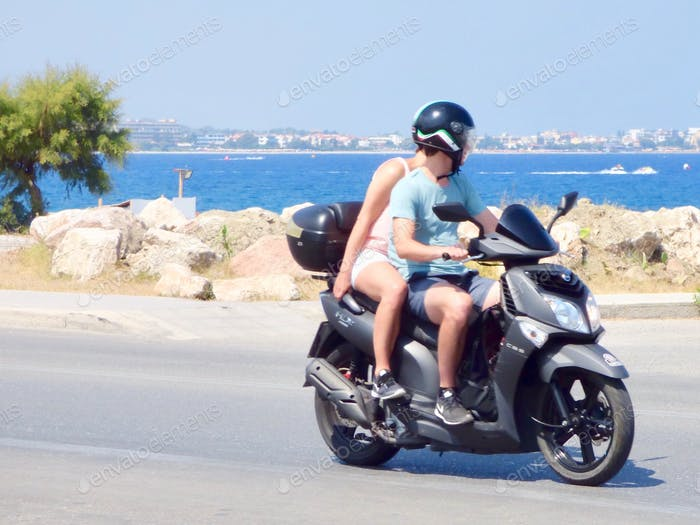 ROAD TRIP ADVENTURE, DISCOVERY: TWO TOURISTS RIDING MOTORBIKE TAKING IN THE  WONDERFUL COASTAL VIEWS