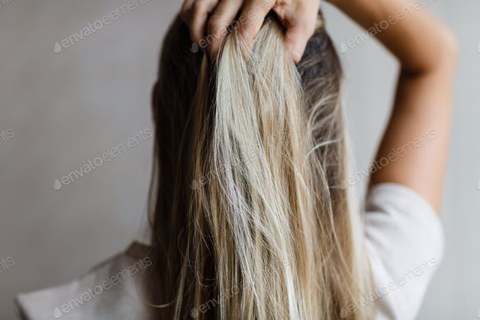 ⭐️⭐️⭐️ Nominated ⭐️⭐️⭐️   Woman holding hand her long blonde hair. View from behind. Coloration. Om