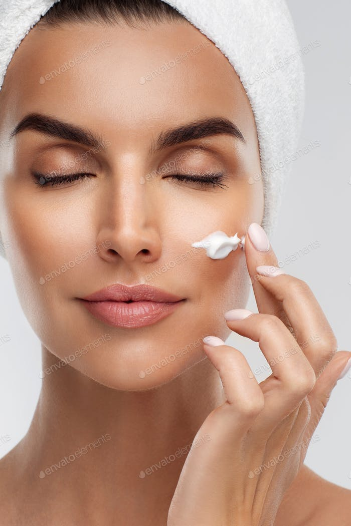Half naked young woman applying moisturizing face anti-aging cream on flawless skin, closed eyes
