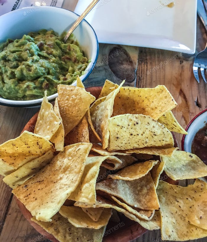Food & drink - fresh guacamole and tortilla chips ready to eat.  Table, crunchy, green, neutral