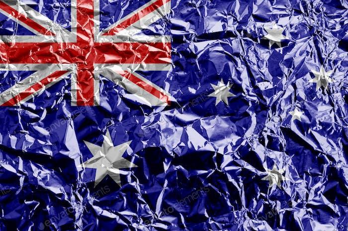 Australia flag depicted in paint colors on shiny crumpled aluminium foil close up