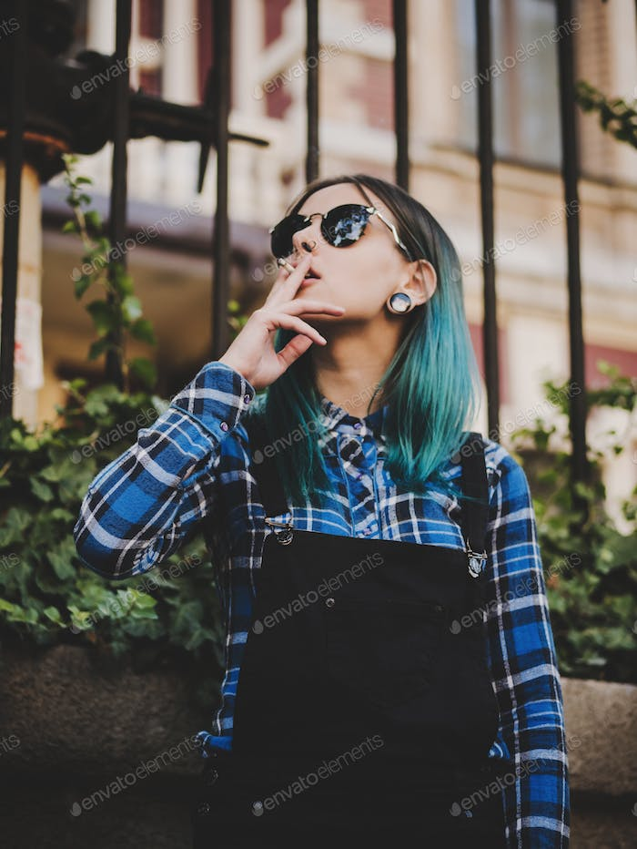 Portrait of Young girl with blue hair smoking cigarette