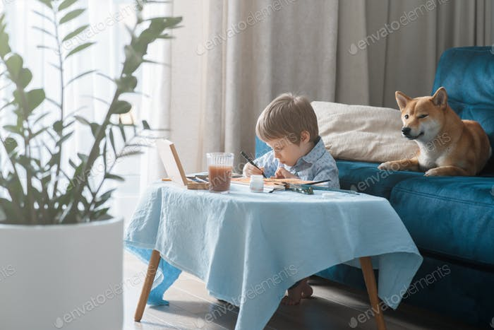 Cute preschool boy painting at home during lockdown, using watercolors and colored pencils