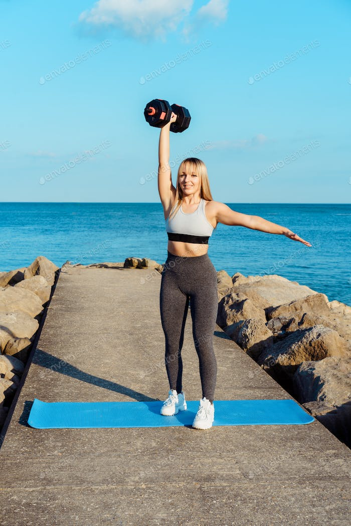Athlete woman working with dumbbells during workout sessions outdoor on the seaside pier.
