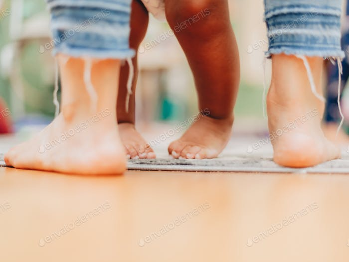 Close up of feet of baby learning to walk