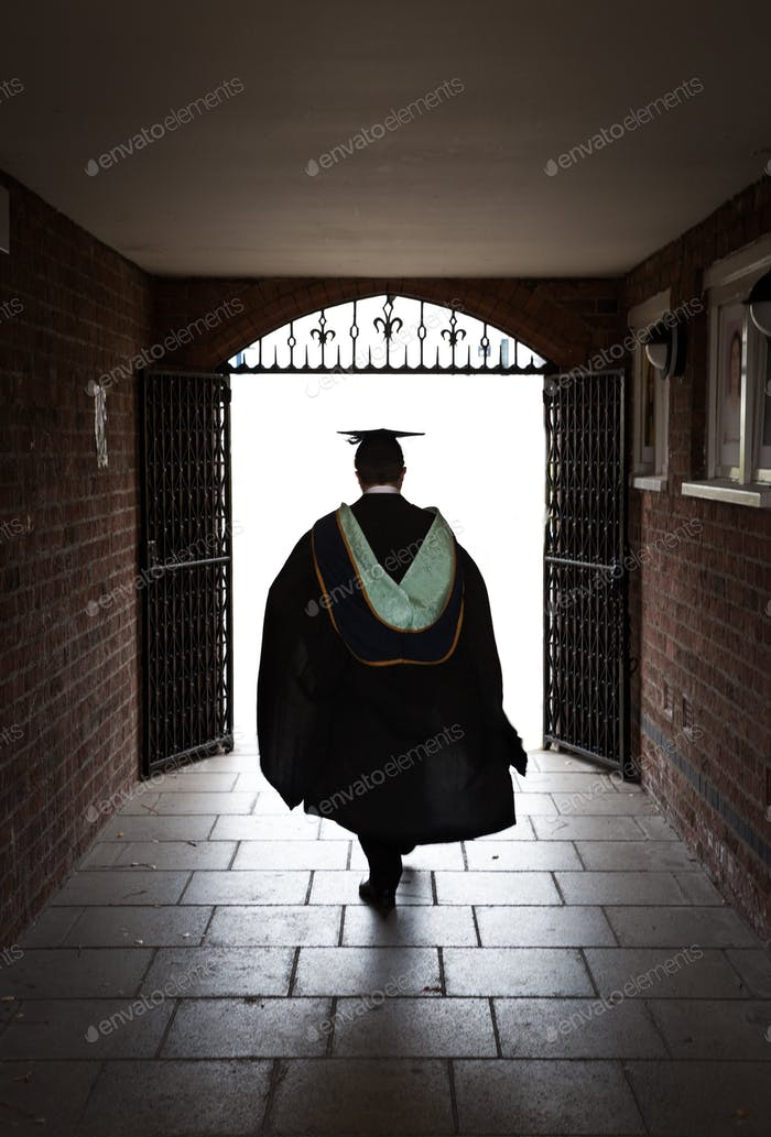Male University Graduate in gown and mortar board walking towards a bright future career