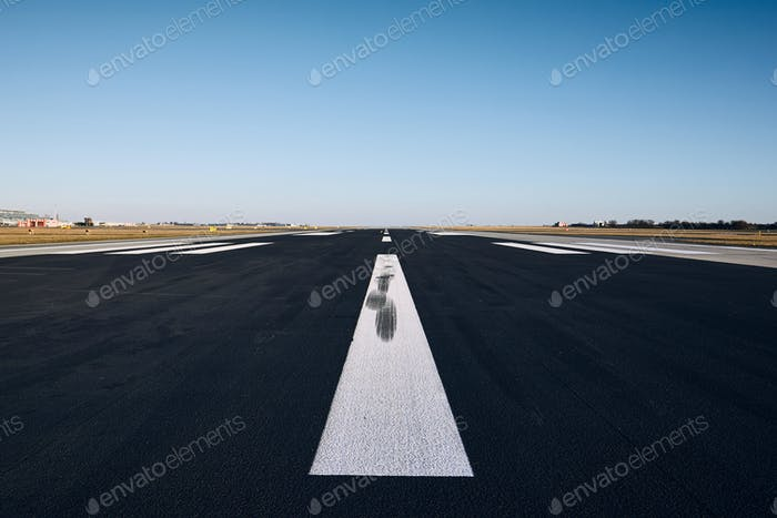 Surface level of airport runway with road marking against clear sky.