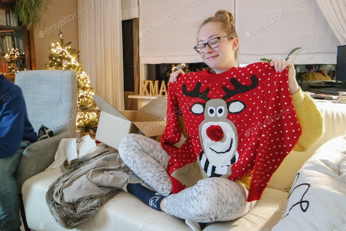 Girl getting presents for Christmas. Very happy with her ugly sweater.