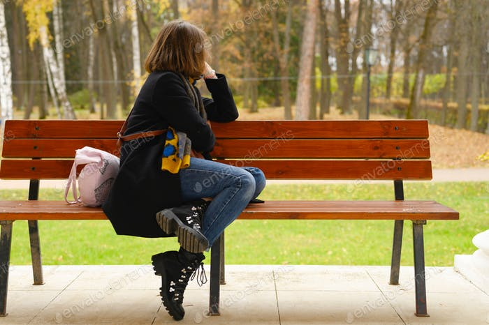 autumn time. beautiful woman dressed up in fall fashion. the girl sits on a bench and looks at the a