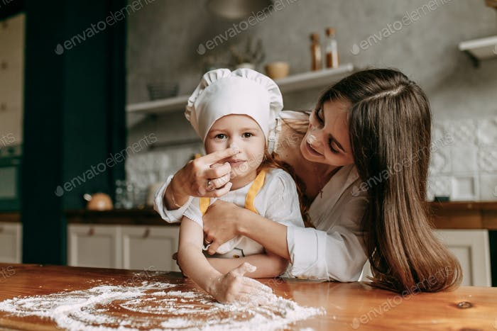 young mother and her little red daughter in an apron cook in the kitchen at home