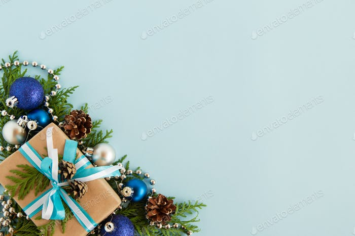 Christmas flat lay composition of fir branches with gift box and decorations at the left bottom