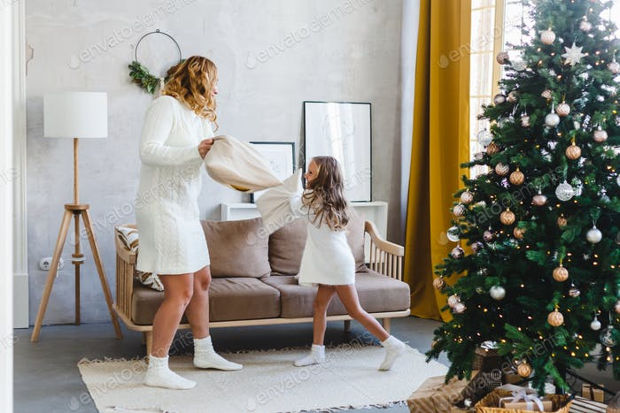 Girl and mother fight with pillows, games and entertainment before the new year and Christmas, the h