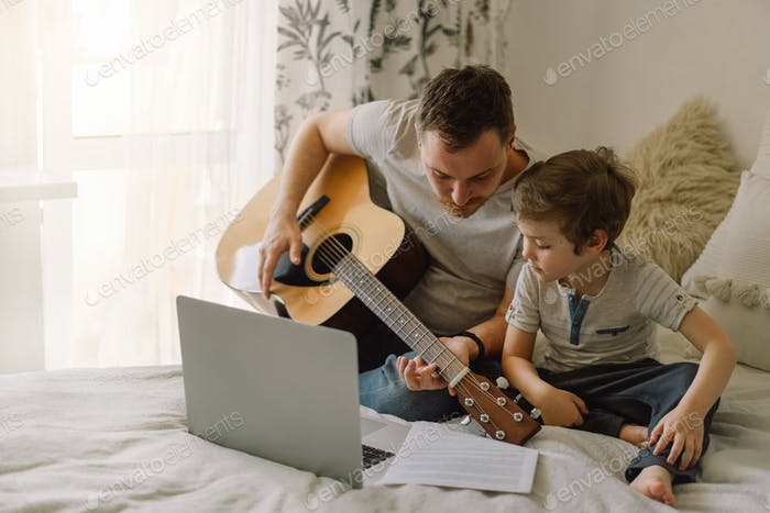Father and son learn to play the acoustic guitar in an online lesson.