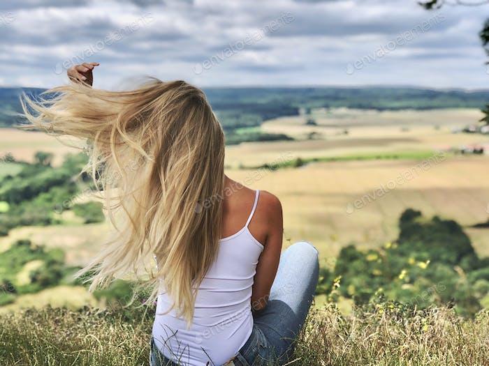 Schönheit in der Natur, junge Frau, mit Haaren spielen, Sitzen, Rückansicht