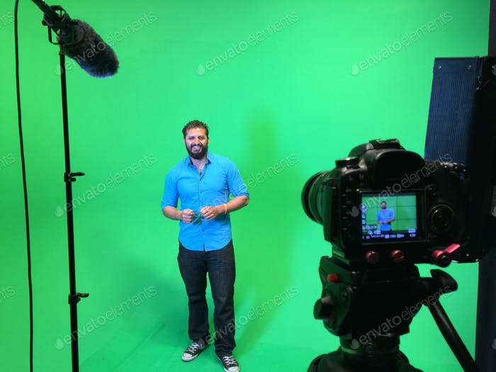 Man with blue shirt being interviewed on a green screen. (Me)