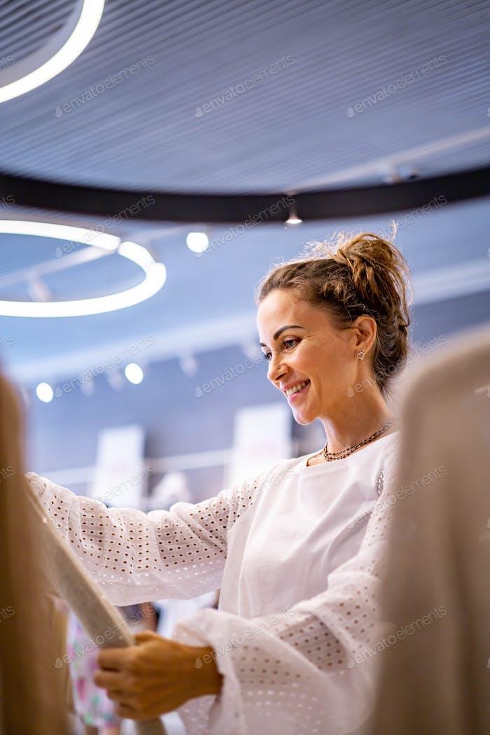 Mujer feliz compradora relajante disfrutando de 50 por ciento de venta en boutique de moda eligiendo ropa