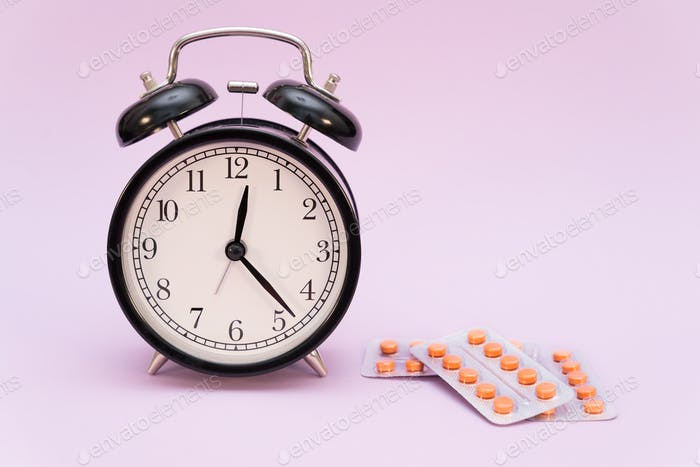 alarm clock and melatonin pills on colored background