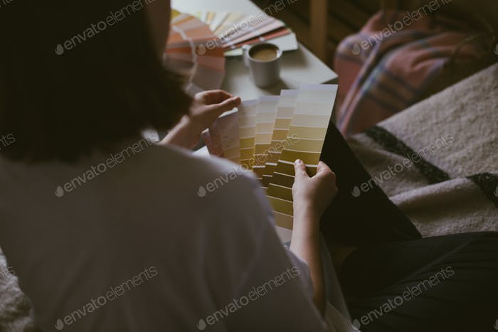 Woman choosing paint colour from swatch for home repair sitting on a couch, drinking coffee.