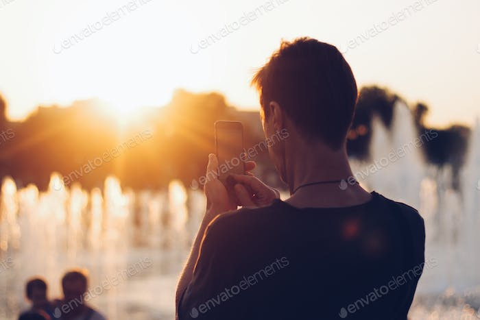 The man takes photo on sunset