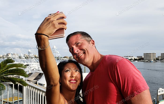Millenial couple taking a selfie outside a seafood restaurant on the harbor at the beach...