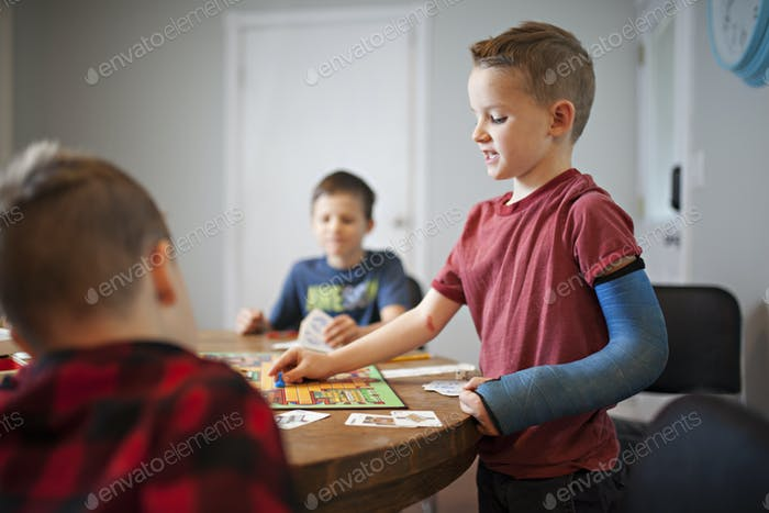 three boys playing an intense board game of clue at the kitchen table