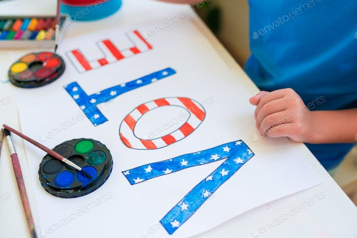 Close-up of a child girl drawing the word Vote. Vote symbol in the American elections.
