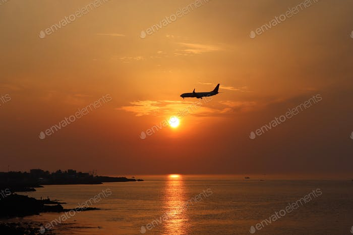 An airplane hovering above the horizon while the sun sets