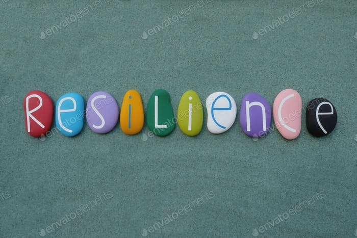Resilience word composed with multicolored handmade painted stone letters over green sand