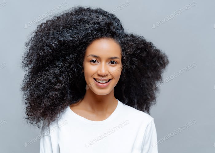 Positive curly woman with natural beauty, dressed in white casual t shirt, has happy expression