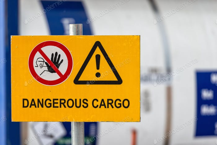 Signs warn of job security. Sign 'dangerous cargo'.