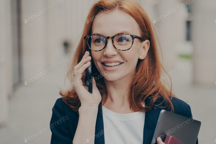 Smiling positive red-haired business woman wearing spectacles calling partner, standing outdoors