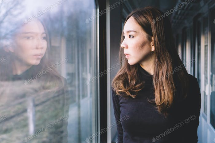 Woman looking through window on the train