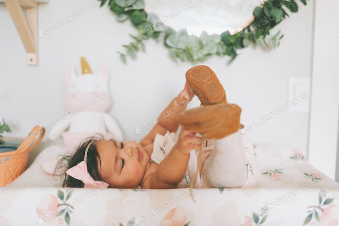 A baby girl touching her toes at home.